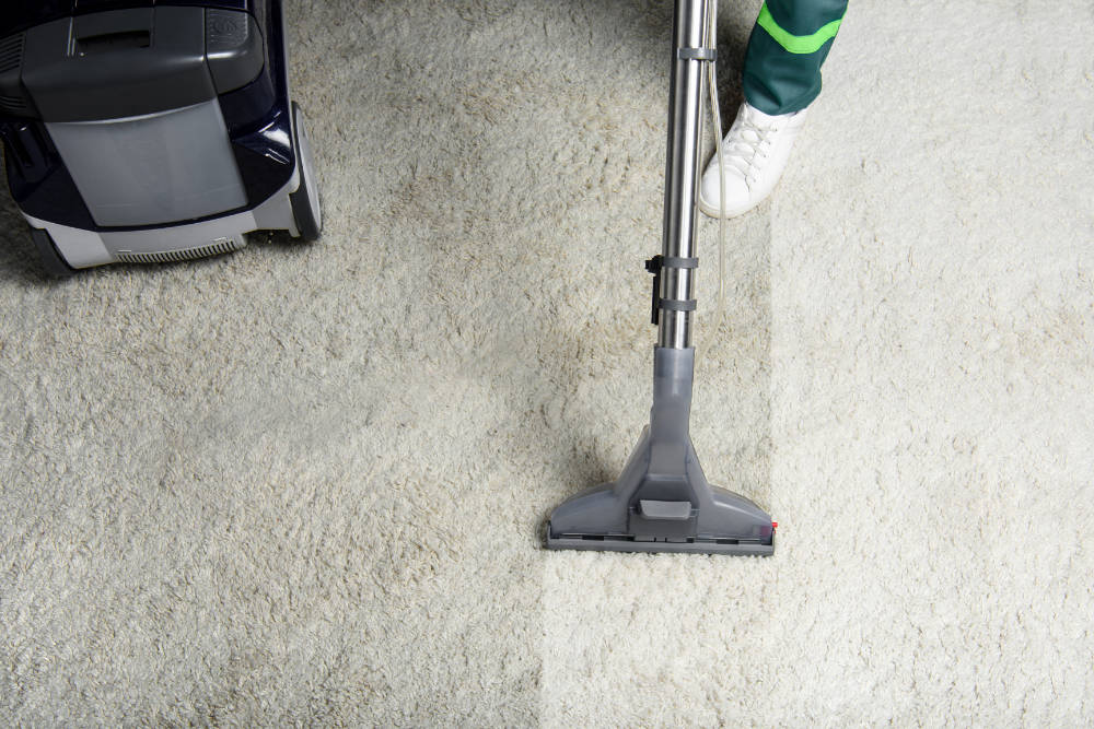 high-angle-view-of-person-cleaning-white-carpet-wi-75MUUW2.jpg